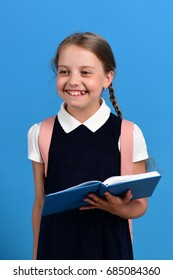 Girl holds big blue book or notebook. School girl with happy smiling face isolated on blue background. Pupil in school uniform with braids and backpack. Back to school and education concept