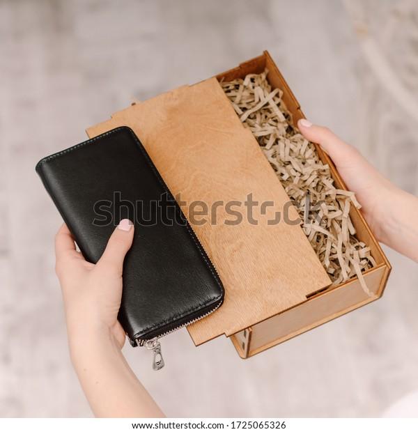 黒い革の財布と木のギフトボックスを持つ女の子
