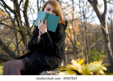 girl holds book in the autumn park