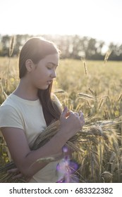 The girl holds a bouquet of wheat spikes