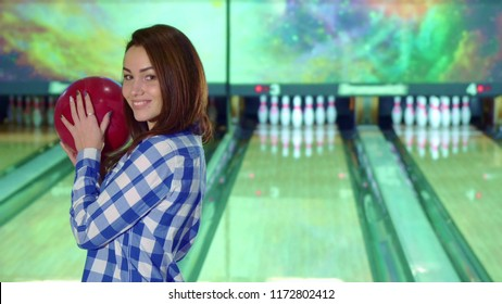 Girl holds bowling ball in her hands