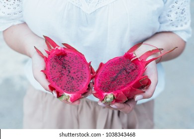 girl holds a bright dragon fruit