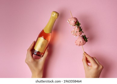 A girl holds a champagne and chocolate-covered strawberries in her hand, on a pink background.