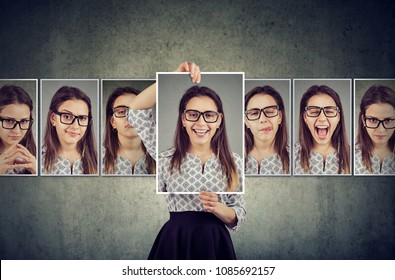 Girl holds and changing her face portraits with different expressions. Woman expressing different emotions