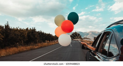 Girl holds colorful balloons out of car window. Freedom, happiness and celebration concept. Letterbox format.
