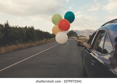 Girl holds colorful balloons out of car window. Freedom, happiness and celebration concept.