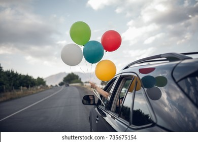 Girl holds colorfull balloons out from the window of the car. Freedom, happyness and celebration concept.