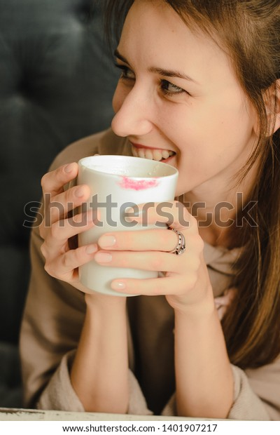 A girl holds a cup of coffee with a lipstick imprint. Beautiful girl laughs over a cup of morning tea.