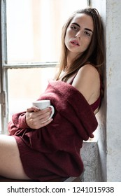 Girl holds a cup of Coffee or Tea looking at the camera near window wearing a long sleve sweater fo wine color