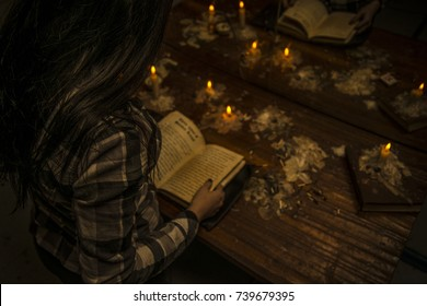 The girl holds a dark ritual reading a spell from the book of Satan. Dangerous and evil magic.