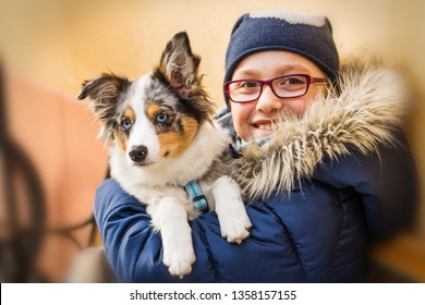 Girl holds dog in her arms