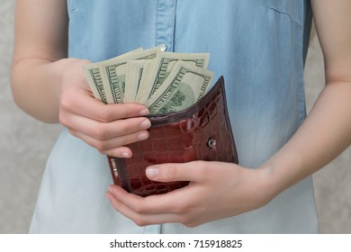 the girl holds dollars in her hands