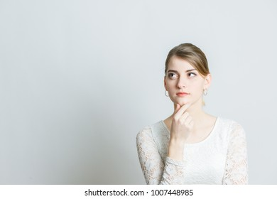 girl holds a finger near her chin and thinks what will happen if, on a white background in the studio