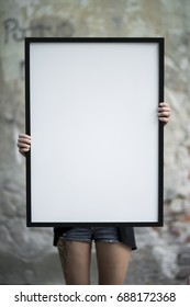 Girl holds a frame on the street for a poster presentation