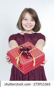 The girl holds a gift. Age 10 years.