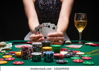 Girl holds a glass of wine. Poker player shows a winning combination in cards against the background of chips, money. Concept of a casino, gaming hall, winners and win. Nightlife success.