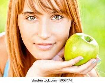Girl holds green apple, against summer grass.