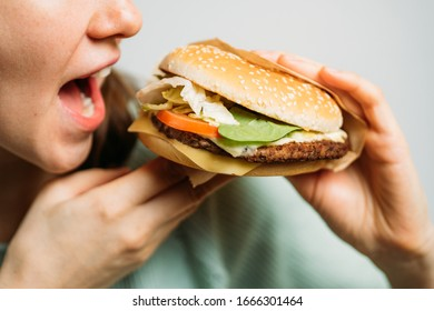 The girl holds a hamburger with her hands and eats it with appetite. Close up.