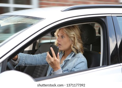 Girl holds a handy in her hand while driving a car and looks horrified
