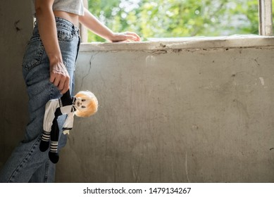 girl holds a harlequin doll in her hands, standing near the window. The concept of sadness and loneliness. The problem of domestic violence, abandoned children