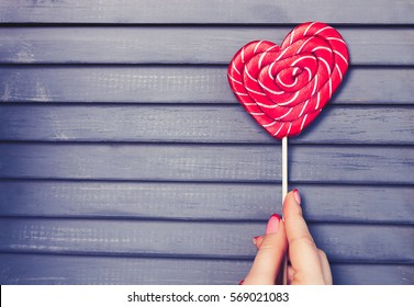 Girl holds heart shaped red candy on stick.Sweet decorative food for Saint Valentines Day celebration.Celebrate 14 February with decorated sweets.Place text on background