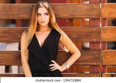 The girl holds her hand on the waist near the wooden fence. close up