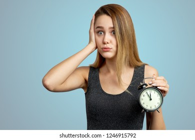 The girl holds her head, sighs, realizes that she was late. Clock at five minutes to twelve. Isolated on blue background in Studio.