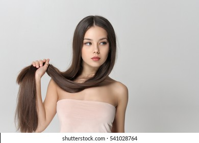 Girl holds her long hair on her arm. Beautiful woman with bare shoulders has a clean well-groomed skin and long straight hair. Close-up portrait against a light gray background.