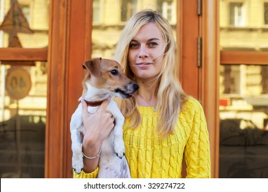 Girl holds a jack russell terrier dog against the backdrop of a door with windows