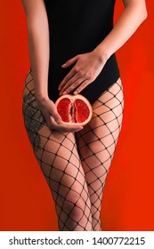 A girl holds a juicy grapefruit. Fruits in the bikini area. Abstraction of fruit. The image speaks of the imminent arrival of female critical days. Bikini area on a red background. Vagina