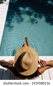A girl holds a light hat with her hands, which covers the whole body, sitting by the pool in the sun with her back to the camera