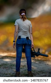 girl holds a machine gun and looks forward and in the back pockets of jeans stores from the machine