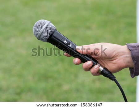 Girl holds microphone on grass field