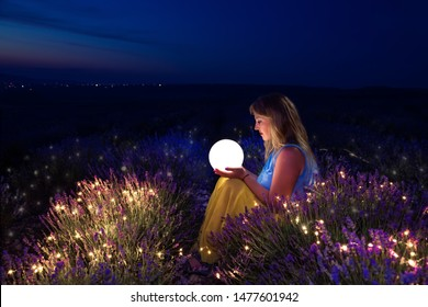 The girl holds the moon in her hands. Lavender field at night. The concept of happiness and freedom. Dreams come true. Everything is possible.