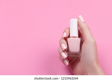 girl holds nail polish with a beautiful manicure