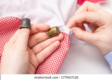 The girl holds a needle and two thimbles in her hands. Vintage thimble. Sewing. Against the background of pink and white fabric.