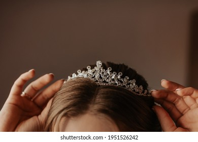 the girl holds on her head a tiara crown decorated with precious stones, young woman bride straightens accessories on her head and ears