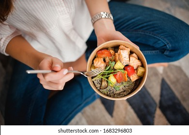 Girl holds a paper plate with healthy food sitting on the floor. Home delivery food. Healthy eating concept. When you stay at home.