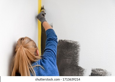 Girl holds a roller in hand close-up. Girl repaints the wall in gray. Repair in the room. DIY repair.
