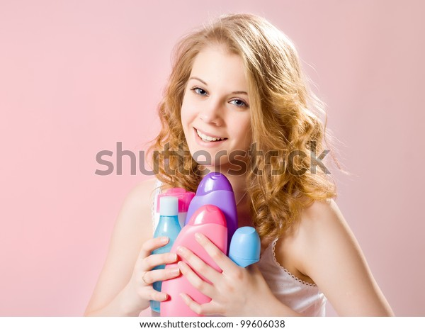 girl holds shampoos conditioners and shower gel