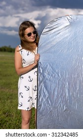 Girl holds a silver reflector for a photoshoot outdoors on a sunny day