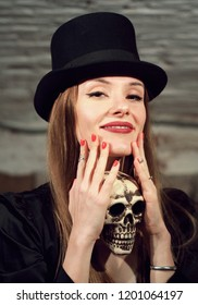 Girl holds skull and smile. Halloween party gothic concept. Woman in black top hat portrait.