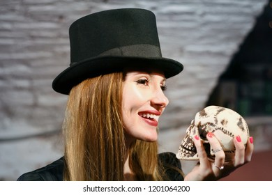 Girl holds skull and smile. Halloween party concept. Young woman in black top hat