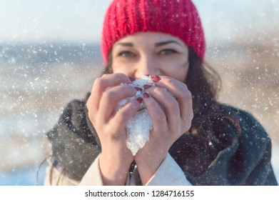 girl holds snow in her hands like a heart