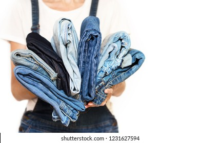 The girl holds a stack of jeans in her hands. cleaning in the closet.