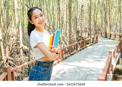 A girl holds three books at her chest in the mangrove forest.