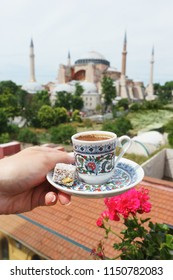 Girl holds a traditional cup of coffee in his hand with a mosque Ayasofya background. Travel to Istanbul, Turkey. Soft focus and beautiful bokeh.
