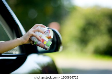 Girl holds trash outside the car window. A woman is about to throw waste out of a car. Environmental pollution, selective focus, backlight