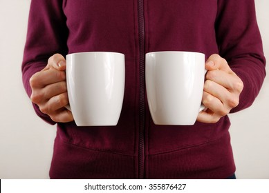 The girl holds two mugs in their hands