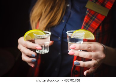 Girl holds two shots of tequila